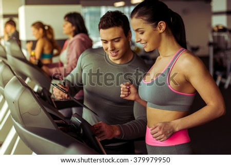 Attractive young woman running on a treadmill in gym, handsome muscular trainer helping her - stock photo