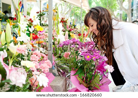 Attractive young woman shopping in an outdoors fresh flowers market stall, buying and picking from a large variety of colorful floral bouquets during a sunny day in the city.
