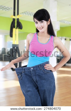 Attractive young woman showing her old jeans at the gym center after doing lose weight program - stock photo