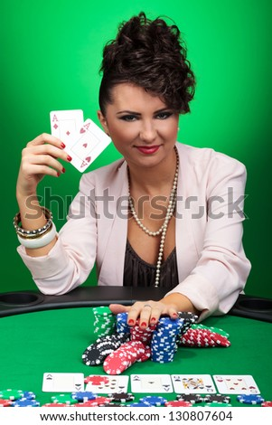 attractive young woman showing you her aces while going all in with a smile on her face. on green background