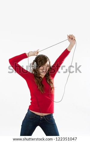 Attractive young woman singing and dancing while listening to music on her headphones, wearing a red top, isolated against a white background.