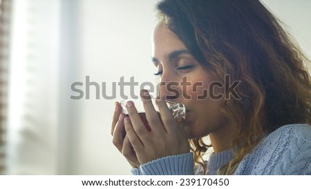 Attractive young woman sipping her hot drink in the morning in a kitchen with her eyes closed in tranquility - stock photo