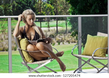 Attractive young woman sitting and reading on balcony overlooking a golf course