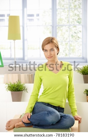 Attractive young woman sitting at home in vivid green pullover, smiling.? - stock photo