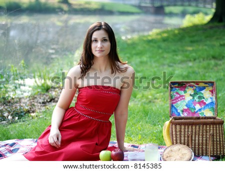 Attractive young woman sitting by picnic basket on blanket