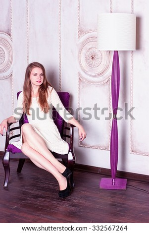 Attractive young woman sitting  in a chair next to a floor lamp. Vertical shot.