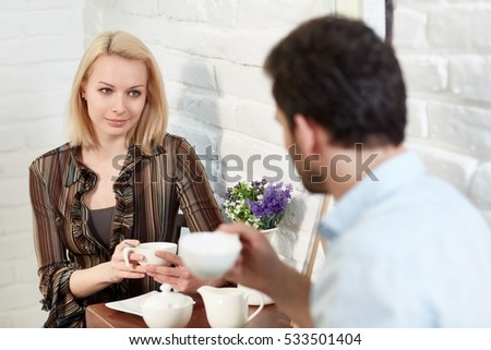 Attractive young woman sitting in cafeteria with boyfriend.