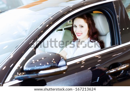Attractive young woman sitting in car in car center
