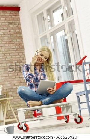 Attractive young woman sitting in retro home, talking on mobilephone using tablet computer. - stock photo
