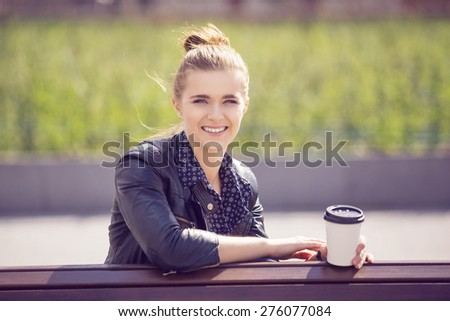 Attractive young woman sitting on a bench with coffee - stock photo