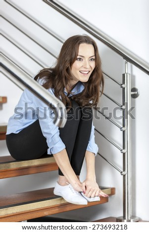 Attractive young woman sitting on a modern staircase waiting and relaxing