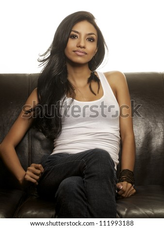 Attractive young woman sitting on leather couch - stock photo