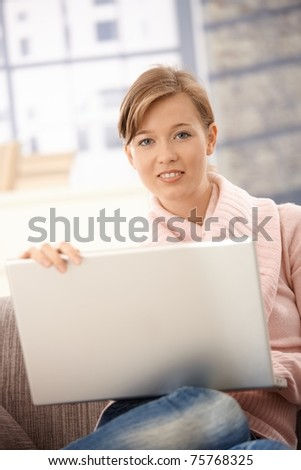 Attractive young woman sitting on sofa at home, using laptop computer. - stock photo
