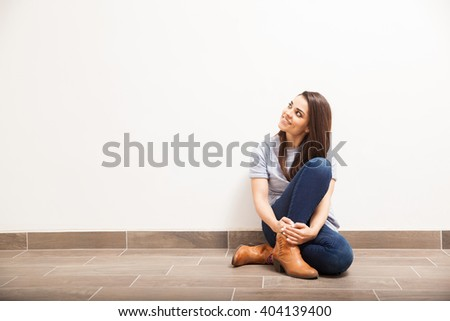 Attractive young woman sitting on the floor against a white wall and looking towards a lot of copy space