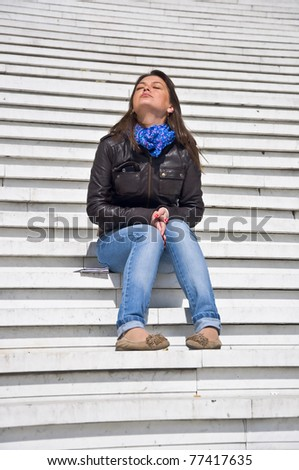 Attractive young woman sitting on the marble steps and tans. Sunlight. Eyes closed.