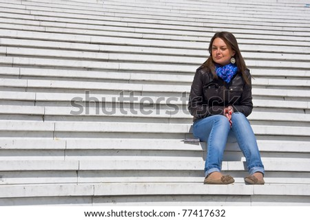 Attractive young woman sitting on the marble steps squinting in the sunlight.