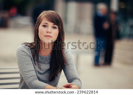 Attractive Young Woman Sitting outside serious - stock photo