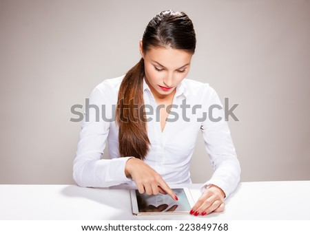 Attractive young woman sitting with tablet.