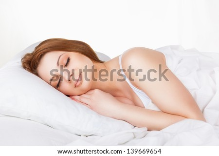 Attractive young woman sleeping in bed - stock photo