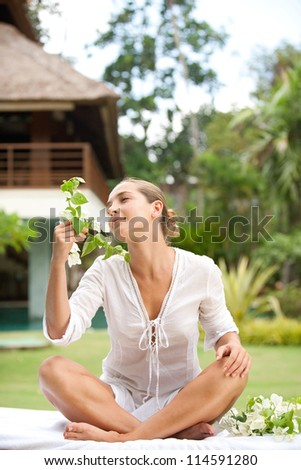 Attractive young woman smelling tropical flowers in an exotic spa garden. - stock photo