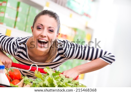 Attractive young woman smiling and pushing a cart at supermarket. - stock photo