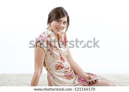 Attractive young woman smiling while listening to music with her earphones at home, sitting on a furry carpet. - stock photo