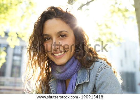 Attractive young woman smiling whilst sitting outdoors on a bright sunny day - stock photo