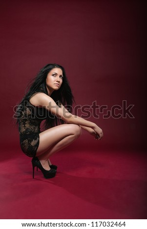 Attractive young woman squating in a seductive pose. She is wearing black underwear. Vertical shot. - stock photo
