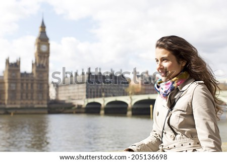 Attractive young woman standing by the River Thames in London with Big Ben and Houses of Parliament blurred out in the background - stock photo