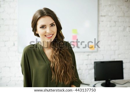 Attractive young woman standing in office against white brick wall - stock photo