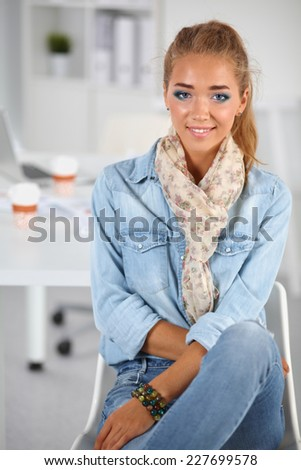 Attractive young  woman standing in office, isolated - stock photo