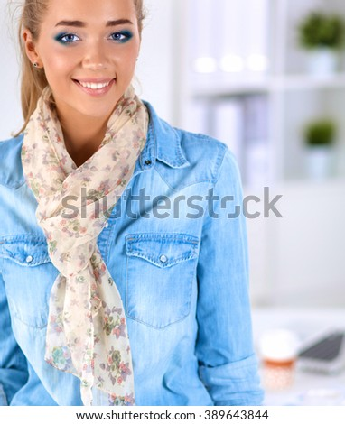 Attractive young  woman standing  near table in office - stock photo