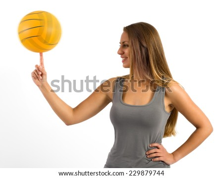 Attractive young woman standing sideways balancing a ball on the tip of her finger her finger with a pleased smile, isolated on white - stock photo