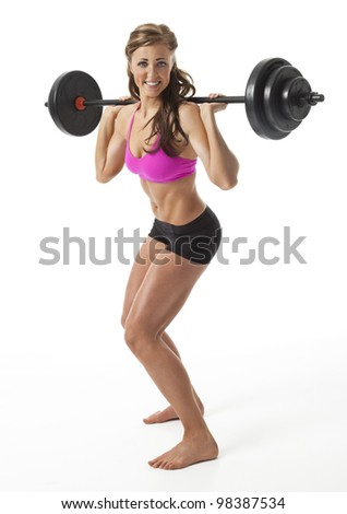 Attractive young woman standing with barbell on shoulders against white background. - stock photo