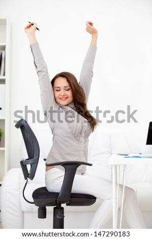 attractive, young woman stretching at her workplace and smiling in the office