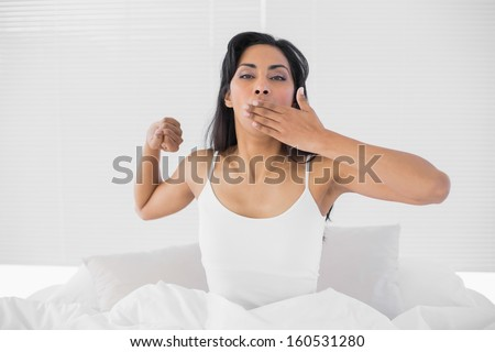 Attractive young woman stretching out and yawning while sitting on her bed in bright bedroom - stock photo