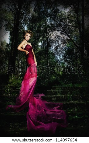 Attractive young woman supermodel standing on stairs in the park - series of photos outdoor