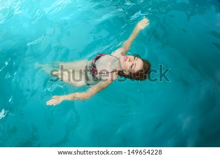Attractive young woman swimming on a spa's pool. Beauty portrait in water - stock photo