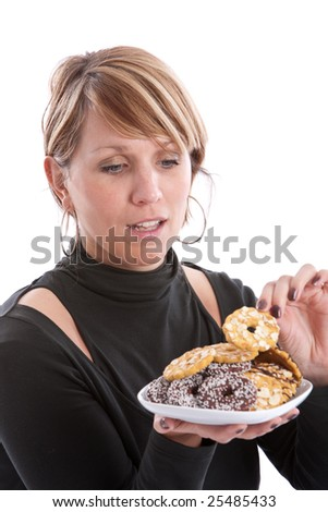 Attractive young woman taking a cookie from the plate