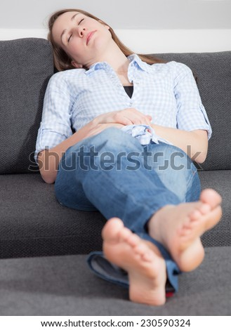Attractive young woman taking a nap on the couch - stock photo