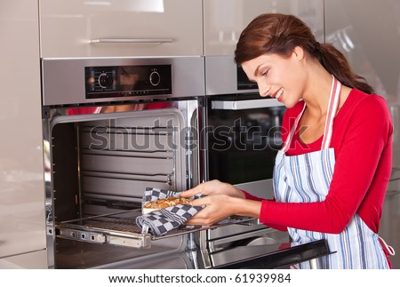 Attractive young woman taking her baked cake out of the oven - stock photo