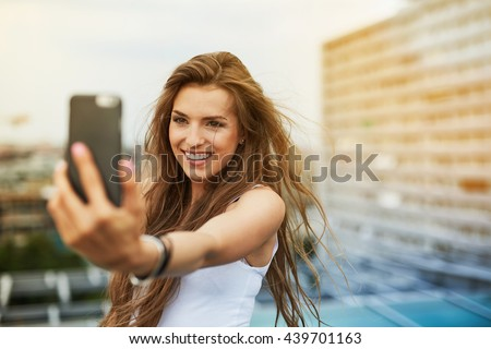 Attractive young woman taking selfie on the rooftop