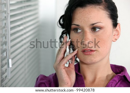 Attractive young woman talking on her mobile phone - stock photo