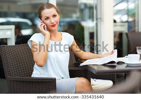 Attractive young woman talking on the cell phone and reading a newspaper in a coffee shop - stock photo
