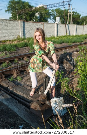 Attractive young woman throws old style railway switch