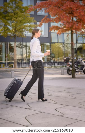 Attractive young woman tourist pulling a trolley down the street on her summer vacation with parked bicycles and cars behind - stock photo