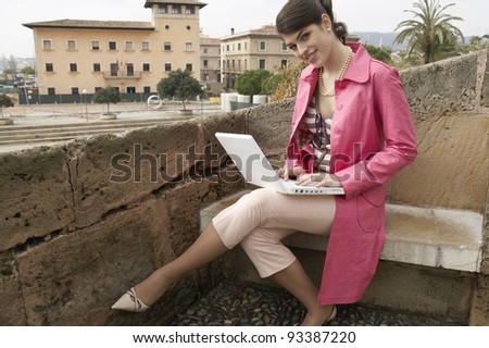 Attractive young woman using a laptop outdoors. - stock photo