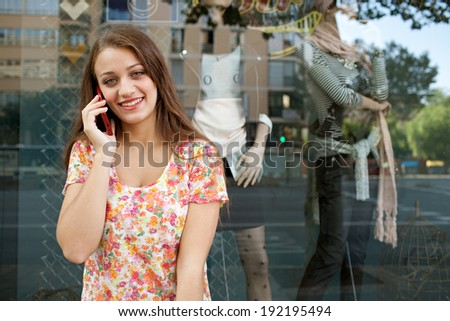 Attractive young woman using a smartphone to have a call conversation while shopping in a city by a fashion store window with reflections on holiday, outdoors. Consumer and technology lifestyle.