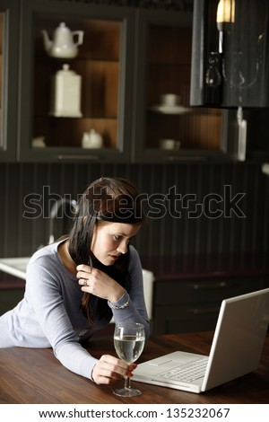 Attractive young woman using her laptop in the kitchen