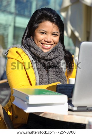 Attractive young woman using laptop in outdoor cafe